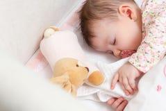 睡觉在有安慰者和玩具的一个轻便小床的女婴 免版税库存照片