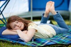 睡觉在有帐篷的毯子的女孩在背景中 免版税库存图片