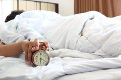 睡觉在有把柄的卧室的人闹钟早晨,健康概念 库存照片