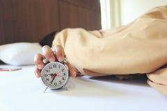 睡觉在有把柄的卧室的年轻女人闹钟早晨,健康概念 库存照片
