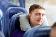 睡觉在有枕头的旅行公共汽车上的愉快的年轻人 免版税库存图片