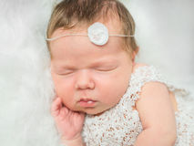 睡觉在有玩具的蓬松格子花呢披肩的美丽的新出生的女孩 免版税库存照片