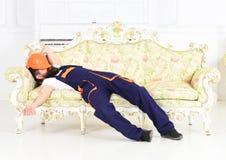 睡觉在有防护盔甲的葡萄酒沙发的有胡子的工作者在他的面孔 有疲乏的建造者享受断裂和 免版税库存图片