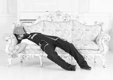 睡觉在有防护盔甲的葡萄酒沙发的有胡子的工作者在他的面孔 有疲乏的建造者享受断裂和 库存照片