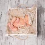睡觉在木背景的箱子的逗人喜爱的赤裸婴孩 免版税库存图片