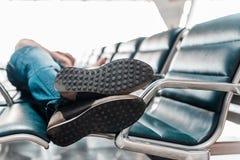 睡觉在机场的年轻人 免版税库存图片