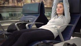 睡觉在机场终端的美丽的可爱的妇女 长途被连接的飞行时差反应 影视素材