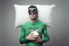 睡觉在枕头的超级英雄漂浮在天空中 免版税库存照片