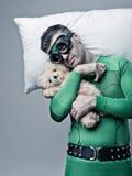 睡觉在枕头的超级英雄漂浮在天空中 免版税库存图片