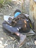 睡觉在树下的无家可归的男孩 免版税库存图片