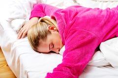 睡觉在桃红色长袍的床上的醉酒的妇女 库存照片