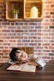 睡觉在桌上的亚裔中国小女孩,当做家庭作业时 库存图片