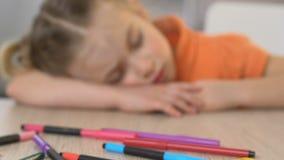 睡觉在桌上的女孩在幼儿园,被用尽在令人疲劳的艺术教训以后,关闭 股票视频