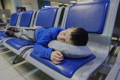 睡觉在椅子的疲乏的小男孩,当等待飞行在机场时 库存图片