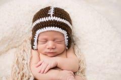 睡觉在橄榄球帽子的新出生的婴孩 免版税库存图片