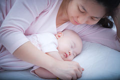 睡觉在母亲胳膊的新出生的女婴 库存图片