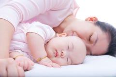 睡觉在母亲胳膊的新出生的女婴 免版税库存照片