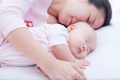 睡觉在母亲胳膊的新出生的女婴 免版税库存图片