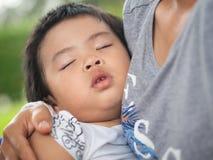 睡觉在母亲` s拥抱的愉快的矮小的逗人喜爱的女孩在公园 家庭,爱,愉快的概念 免版税库存图片