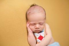 睡觉在毯子的新出生的婴孩 免版税库存照片