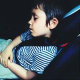 睡觉在汽车的疲乏的男孩 免版税库存照片