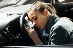 睡觉在汽车的被用尽的妇女 库存图片