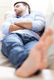 睡觉在沙发的人 免版税库存照片
