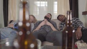 睡觉在沙发的画象两白种人和一非裔美国人的人在观看在电视的拳击以后 空的啤酒瓶 股票录像