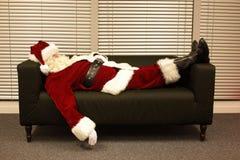 睡觉在沙发的被用尽的圣诞老人 库存照片
