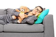 睡觉在沙发的年轻人拿着玩具熊 库存照片