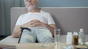 睡觉在沙发,药剂的不适的孤独的祖父站立在桌上 影视素材
