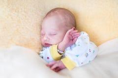 睡觉在温暖的羊皮的甜新出生的婴孩 免版税库存图片