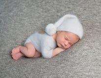 睡觉在滑稽的帽子的新出生的男孩 免版税库存图片