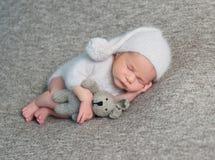 睡觉在滑稽的帽子的新出生的男孩 库存照片