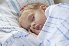 睡觉在火车的一个轻便小床的四岁的女孩 免版税库存照片