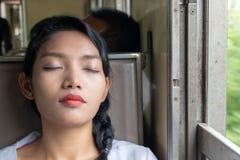 睡觉在火车的年轻女人画象 免版税库存图片