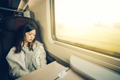 睡觉在火车的美丽的亚裔女孩,当听到音乐,与拷贝空间,软的温暖的轻的口气时 库存照片