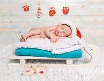 睡觉在爬犁轻便小床的赤裸新出生的婴孩 库存照片