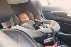 睡觉在现代汽车座位的亚裔逗人喜爱的新出生的婴孩 库存图片