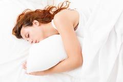 睡觉在白色枕头的俏丽的女孩 库存照片