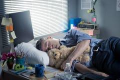 睡觉在的办公室工作者与玩具熊一起使用 图库摄影