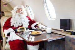 睡觉在私人喷气式飞机的圣诞老人 库存照片