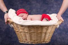 睡觉在篮子的新出生的婴孩由父母举行了 库存照片