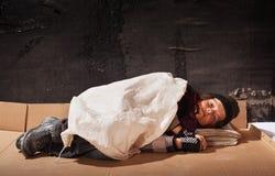 睡觉在纸板板料的叫化子男孩 免版税库存图片