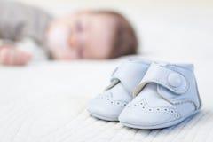 睡觉在背景的浅蓝色鞋子和宝贝 免版税库存图片