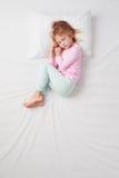 睡觉在胎儿姿势的小女孩顶视图 图库摄影