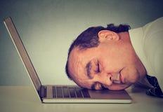 睡觉在膝上型计算机的商人在他的书桌,疲乏的中部变老了人雇员 库存照片
