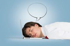 睡觉在膝上型计算机的工作者 免版税库存照片