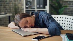 睡觉在膝上型计算机的被用尽的少女在休息在辛苦以后的工作 股票录像