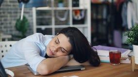 睡觉在膝上型计算机的被用尽的年轻女人在休息在坚硬工作日以后的工作 影视素材